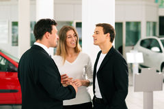 Paar met verkoper bij autohandelaar Royalty-vrije Stock Afbeelding
