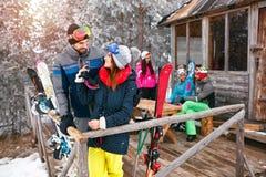 Paar met vrienden die vakantie in het plattelandshuisje van de de wintersneeuw besteden Stock Afbeelding