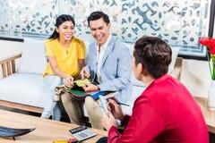 Paar met winkelmedewerker in meubilairopslag Stock Fotografie