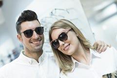 Paar met zonnebril die en camera in glazen glimlachen bekijken stock afbeelding