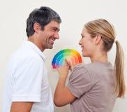 Paar mit Farbe prüft, um ihr neues Haus zu malen Lizenzfreies Stockfoto