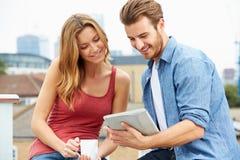 Paar op Dakterras die Digitale Tablet gebruiken Stock Foto's