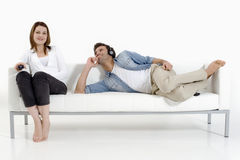 Paar op de laag die op TV let Stock Foto