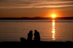 Paar op de strandzonsondergang Royalty-vrije Stock Afbeeldingen
