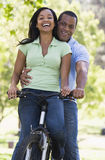 Paar op een fiets die in openlucht glimlacht Stock Foto