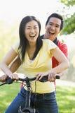 Paar op een fiets die in openlucht glimlacht stock foto's