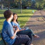 Paar op een Horizontale Bank van het Park - stock afbeelding