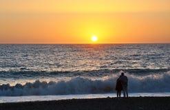 Paar op het strand bij zonsondergang Royalty-vrije Stock Afbeeldingen