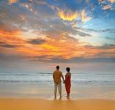 Paar op het strand bij zonsondergang Stock Afbeeldingen
