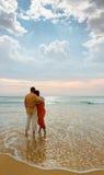 Paar op het strand bij zonsondergang Stock Afbeelding