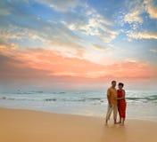 Paar op het strand bij zonsondergang Stock Foto