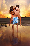 Paar op het strand bij zonsondergang Royalty-vrije Stock Foto's