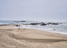 Paar op het strand dichtbij de oceaan stock foto