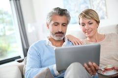 Paar op middelbare leeftijd bij tablet het websurfing royalty-vrije stock foto