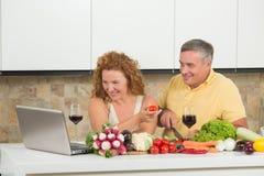 Paar op middelbare leeftijd in de keuken Stock Foto's