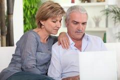 Paar op middelbare leeftijd met een computer stock afbeeldingen