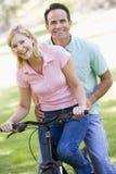 Paar op één fiets die in openlucht glimlacht Stock Foto's