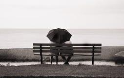 Paar op parkbank met paraplu Stock Foto's
