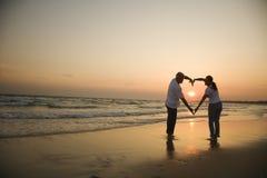 Paar op strand bij zonsondergang.