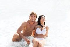 Paar op strand, die in het schuimoverzees van de watergolf zitten Stock Foto