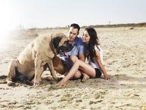 Paar op strand het spelen met huisdierenhond. royalty-vrije stock afbeeldingen