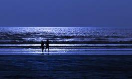 Paar op strand op maan lichte nacht Stock Foto