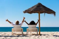 Paar op strandvakantie met zonnescherm Stock Foto
