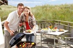Paar op vakantie die barbecue heeft stock afbeelding