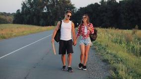 Paar op Vakantie langs Weg het liften en de Holding die ondertekenen overal Jonge volwassenen Lift, toeristen, avonturen stock footage