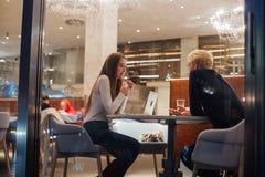 Paar op vergadering of datum bij koffievenster bij nacht stock afbeeldingen