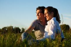 Paar op weide in zonsondergang Royalty-vrije Stock Fotografie