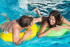 Paar in opblaasbare ringen bij zwembad Stock Foto