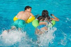 Paar in opblaasbare ringen bij zwembad Royalty-vrije Stock Afbeelding