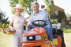 Paar in openlucht met hulpmiddelen en grasmaaier het glimlachen royalty-vrije stock fotografie