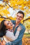 Paar in openlucht in park in de herfst die prettijd hebben Stock Foto's