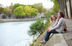 Paar in Parijs, dat bij de rand van water zit Royalty-vrije Stock Fotografie