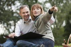 Paar in park met fotoalbum stock foto