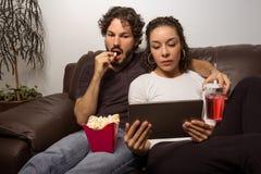 Paar passt Film auf Tablette auf Sie so sitzend auf dem Sofa an h stockbilder
