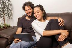 Paar passt on-line-Inhalt auf der Tablette auf Sie so an sitzend lizenzfreies stockbild