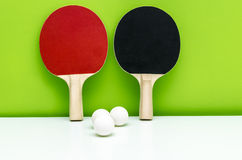 Paar pingpongrackets en witte ballen, op licht gre stock foto