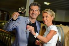 Paar proevende wijn in een kelder royalty-vrije stock afbeeldingen