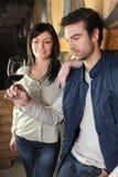 Paar proevende wijn in kelder Stock Afbeeldingen