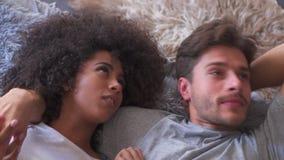 Paar in pyjama's die op bed spreken stock footage