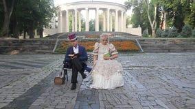 Paar in retro kostuum en kleding die een boek op een bank lezen stock video