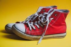 Paar rode gebruikte tennisschoenen op gele kleurrijke achtergrond, mening van kant stock foto
