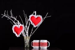 Paar rode harten op een tak met twee mokken Royalty-vrije Stock Afbeeldingen