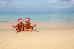 paar in rode Kerstmanhoeden bij tropisch strand Stock Fotografie