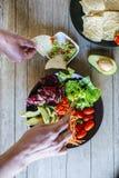 Paar` s handen die avocadosalade en plaat van nac eten Stock Afbeeldingen