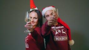 Paar in santahoeden die met champagneglazen clinking en nieuw jaar vieren stock footage