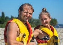 Paar setzt an schwimmende Westen auf Strand Stockbild